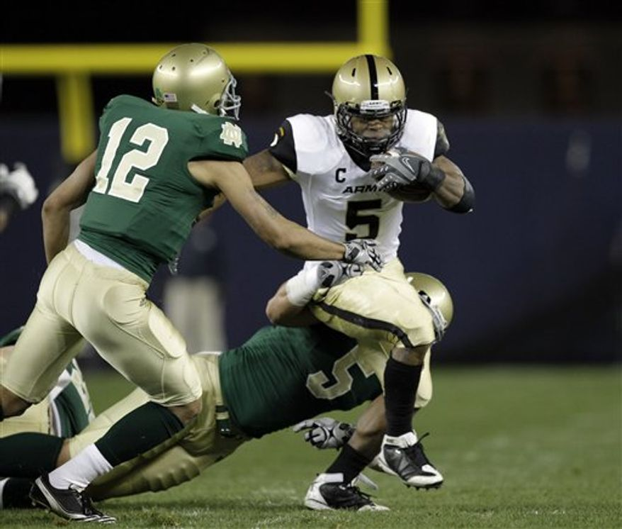Army running back Patrick Mealy (5) tries to escape the grasp of Notre Dame linebacker Manti Te'o (5) as Fighting Irish cornerback Robert Blanton (12) backs him up in the first quarter of an NCAA college football game at Yankee Stadium in New York, Saturday, Nov. 20, 2010.  (AP Photo/Kathy Willens)