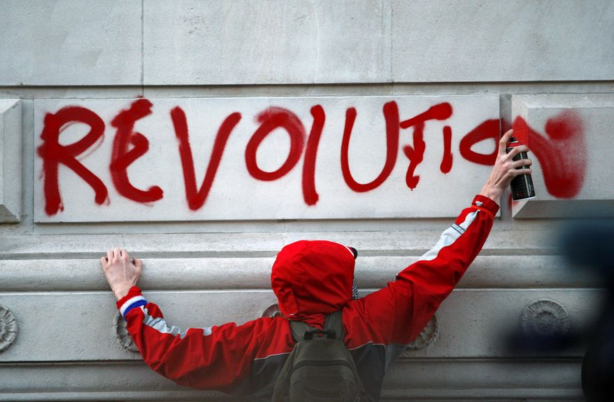 A protester sprays a message on a government building Wednesday as students protest against tuition fees at Whitehall in London. Thousands of British students participated in the demonstration. (Associated Press)