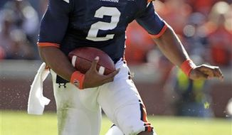 FILE - This Oct. 16, 2010, file photo shows Auburn quarterback Cam Newton running against Arkansas in the first half of an NCAA college football game in Auburn, Ala.,  Newton's status _ and his prodigious talent _ remains the primary topic surrounding No. 2 Auburn leading to the Iron Bowl against No. 9 Alabama.  (AP Photo/Dave Martin, File)