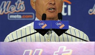 New York Mets General Manager Sandy Alderson, left, assists newly named Mets manager Terry Collins with a jersey during a news conference at Citi Field in New York, Tuesday, Nov. 23, 2010. (AP Photo/Stephen Chernin)