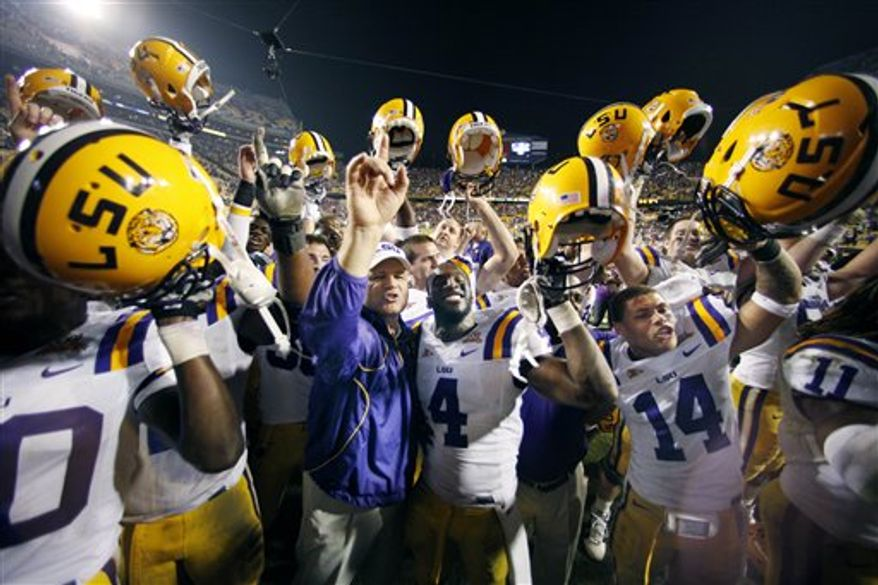 LSU cornerback Patrick Peterson (7) and wide receiver Terrence Toliver (80) hoist up the Magnolia Bowl trophy after their NCAA college football game against Mississippi in Baton Rouge, La., Saturday, Nov. 20, 2010. LSU won 43-36. (AP Photo/Gerald Herbert)