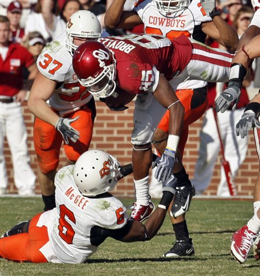 FILE - This Nov. 28, 2009, filemphoto shows  Oklahoma State cornerback Andrew McGee, left, tackling Oklahoma wide receiver Jaz Reynolds, right, in the first quarter of an NCAA college football game in Norman, Okla. When the diagnosis came back that McGee had two cracked vertebrae, everyone immediately thought his football career was over. (AP Photo/Sue Ogrocki, File)