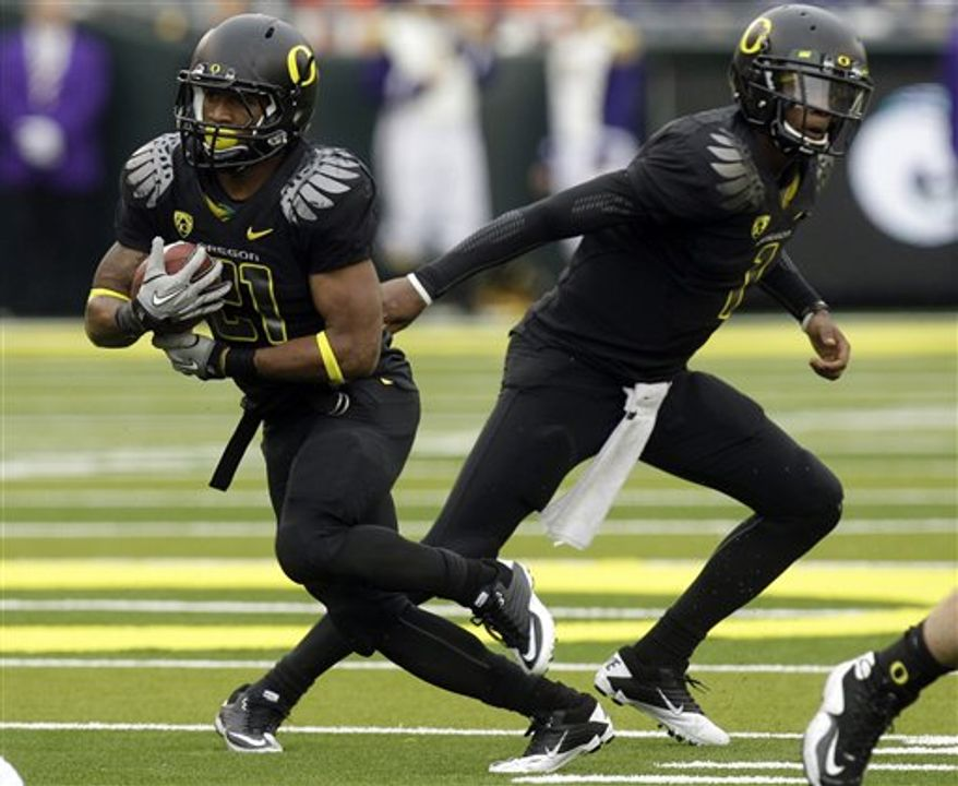FILE - In this Nov. 6, 2010, file photo, Oregon quarterback Darron Thomas (1) hands the ball off to running back LaMichael James (21) during the first half of an NCAA college football game in Eugene, Ore. Top-ranked Oregon boasts what many say is the best offensive duo in the nation, quarterback Darron Thomas and running back LaMichael James. (AP Photo/Rick Bowmer, File)