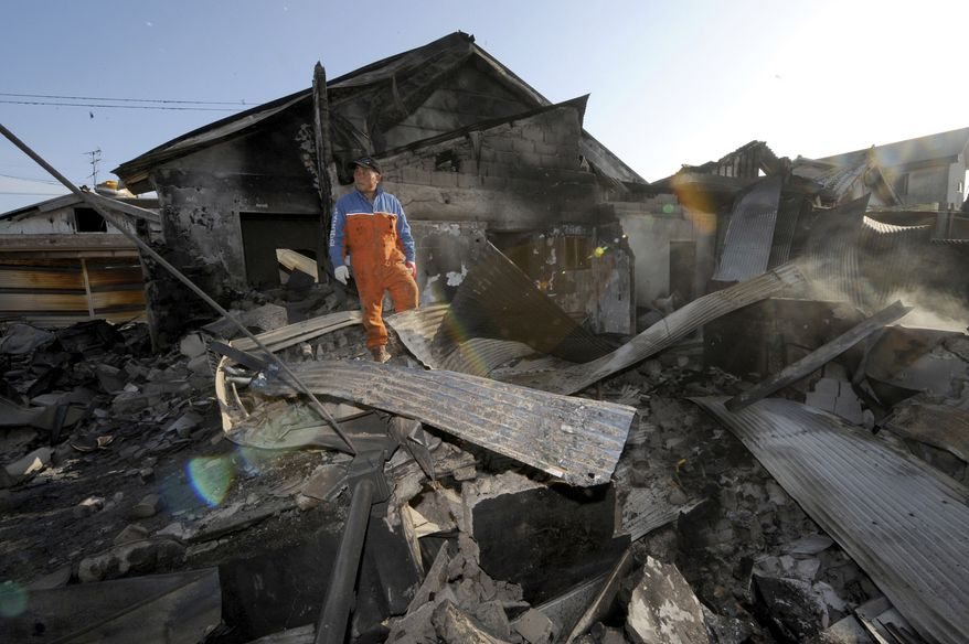 A South Korean resident stands on the rubble of a destroyed house on Yeonpyeong island, South Korea, Wednesday, Nov. 24, 2010. South Korea found the burned bodies Wednesday of two islanders killed in a North Korean artillery attack, marking the first civilian deaths in the incident and dramatically escalating the tensions in the region's latest crisis. (AP Photo/Yonhap)