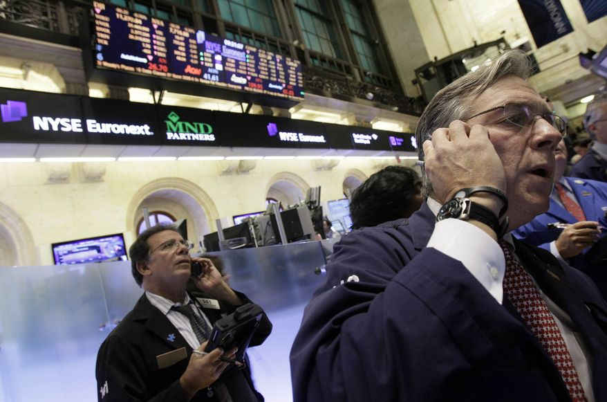 In this file photo taken Nov. 11, 2010, traders work on the floor of the New York Stock Exchange. (AP Photo/Richard Drew, file)