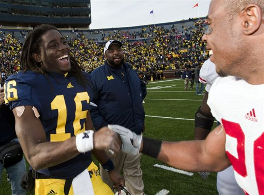 Michigan head coach Rich Rodriguez runs out with his team before the start of an NCAA college football game against Wisconsin in Ann Arbor, Mich., Saturday, Nov. 20, 2010. (AP Photo/Carlos Osorio)