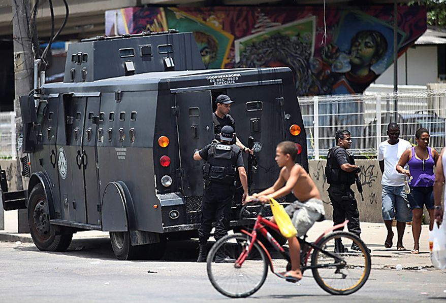 Police patrol in the Manguinhos slum in Rio de Janeiro, Brazil, Tuesday Nov. 23, 2010.  Rio's entire military police force was ordered into the streets after more gang attacks ended with two motorists shot dead, cars burned and mass robberies on highways.  (AP Photo/Silvia Izquierdo)