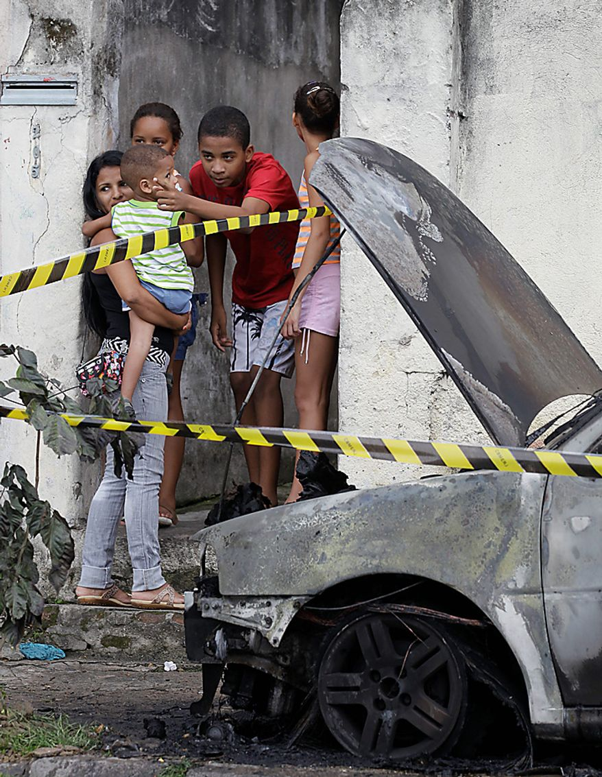 A woman and children stand next a car burned by alleged treffickers at Cavalcanti neighborhood, in Rio de Janeiro, Brazil, Wednesday Nov. 24, 2010. Rio's entire military police force was ordered into the streets after more gang burned cars. (AP Photo/ Silvia Izquierdo)