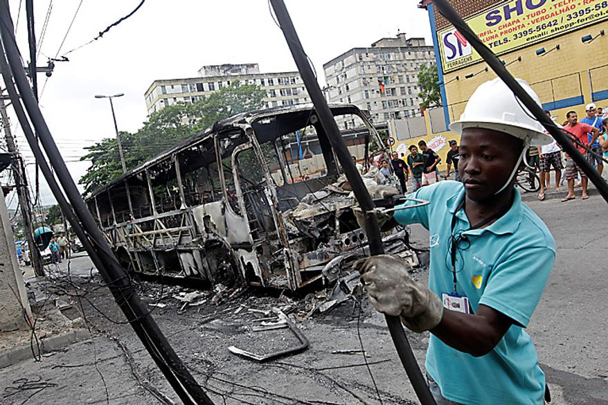 A worker cuts damaged cables next to a bus burned by alleged drug traffickers at the Santa Cruz slum in Rio de Janeiro, Brazil, Wednesday Nov. 24, 2010. Heavily armed men halted buses and cars, robbed their passengers and set the vehicles ablaze Wednesday in Rio de Janeiro, continuing a wave of violence that has rattled rich and poor alike in a city Brazil hopes to make a showplace for the 2016 Olympics. (AP Photo/Silvia Izquierdo)