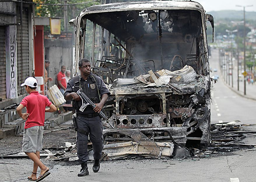 A police officer guards the area where a bus was burned  by alleged drug traffickers at the Santa Cruz slum in Rio de Janeiro, Brazil, Wednesday Nov. 24, 2010. Heavily armed men halted buses and cars, robbed their passengers and set the vehicles ablaze Wednesday in Rio de Janeiro, continuing a wave of violence that has rattled rich and poor alike in a city Brazil hopes to make a showplace for the 2016 Olympics. (AP Photo/Silvia Izquierdo)