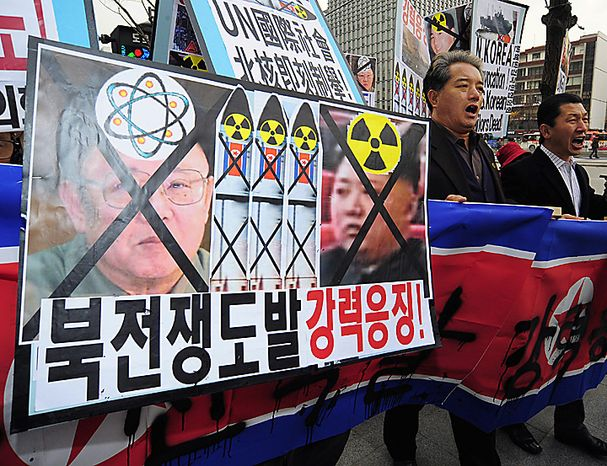 Protesters march with defaced portraits of North Korea leader Kim Jong Il, left, and his son Kim Jong Un, denouncing North Korea's artillery barrages targeting Yeonpyeong island Wednesday, Nov. 24, 2010 in Seoul, South Korea.  (AP Photo/Kyodo News)