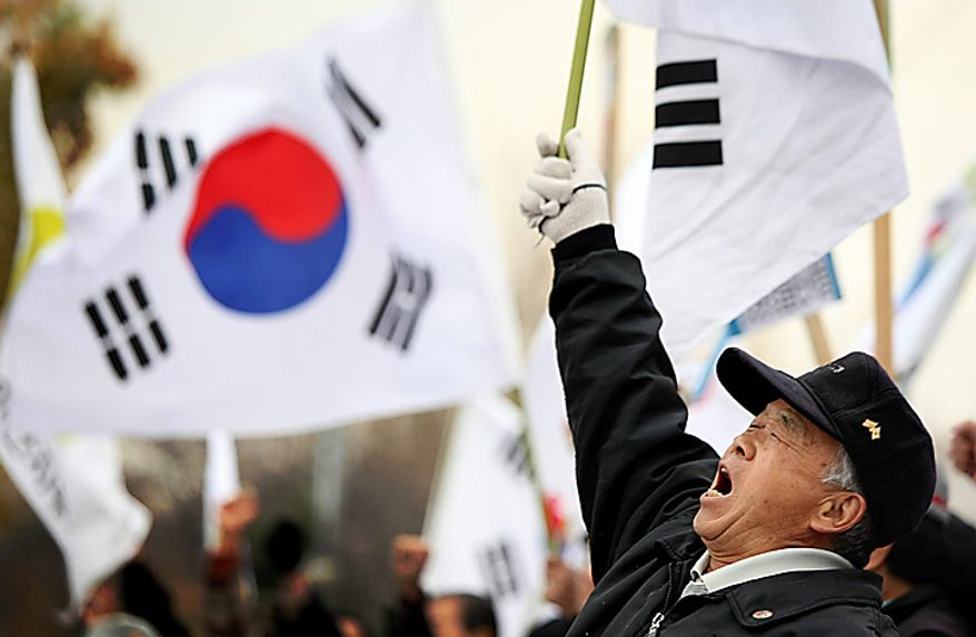Protesters denounce North Korea in front of the Defense Ministry, Wednesday, Nov. 24, 2010 in Seoul, South Korea. South Korea's troops were on high alert Wednesday as their government exchanged threats with rival North Korea following a frightening military skirmish that ratcheted tensions on the peninsula to new extremes. (AP Photo/Wally Santana)