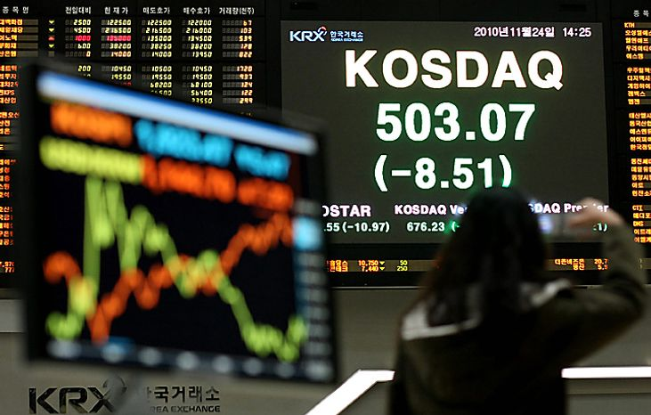 A woman takes a photograph of an electronic stock board at the Korea Stock Exchange in Seoul, South Korea, on Wednesday, Nov. 24, 2010. South Korea's won dropped to a two-month low and stocks declined after North Korea fired artillery at its southern neighbor, killing two soldiers. Government bonds recovered from initial losses. Photographer: SeongJoon Cho/Bloomberg