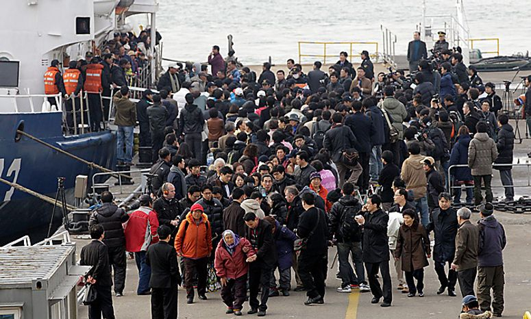 South Korean survivors arrive as they are surrounded by relatives and media at a port in Incheon, west of Seoul, South Korea, Wednesday, Nov. 24, 2010. South Korea's troops were on high alert Wednesday as their government exchanged threats with rival North Korea following a frightening military skirmish that ratcheted tensions on the peninsula to new extremes. (AP Photo/ Lee Jin-man)