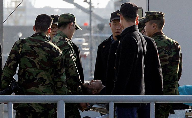 South Korean soldiers carry an injured man upon arrival from the island of Yeonpyeong at a military port in Incheon, west of Seoul, South Korea, Wednesday, Nov. 24, 2010. South Korea's troops were on high alert Wednesday as their government exchanged threats with rival North Korea following a frightening military skirmish that ratcheted tensions on the peninsula to new extremes. (AP Photo/ Lee Jin-man)
