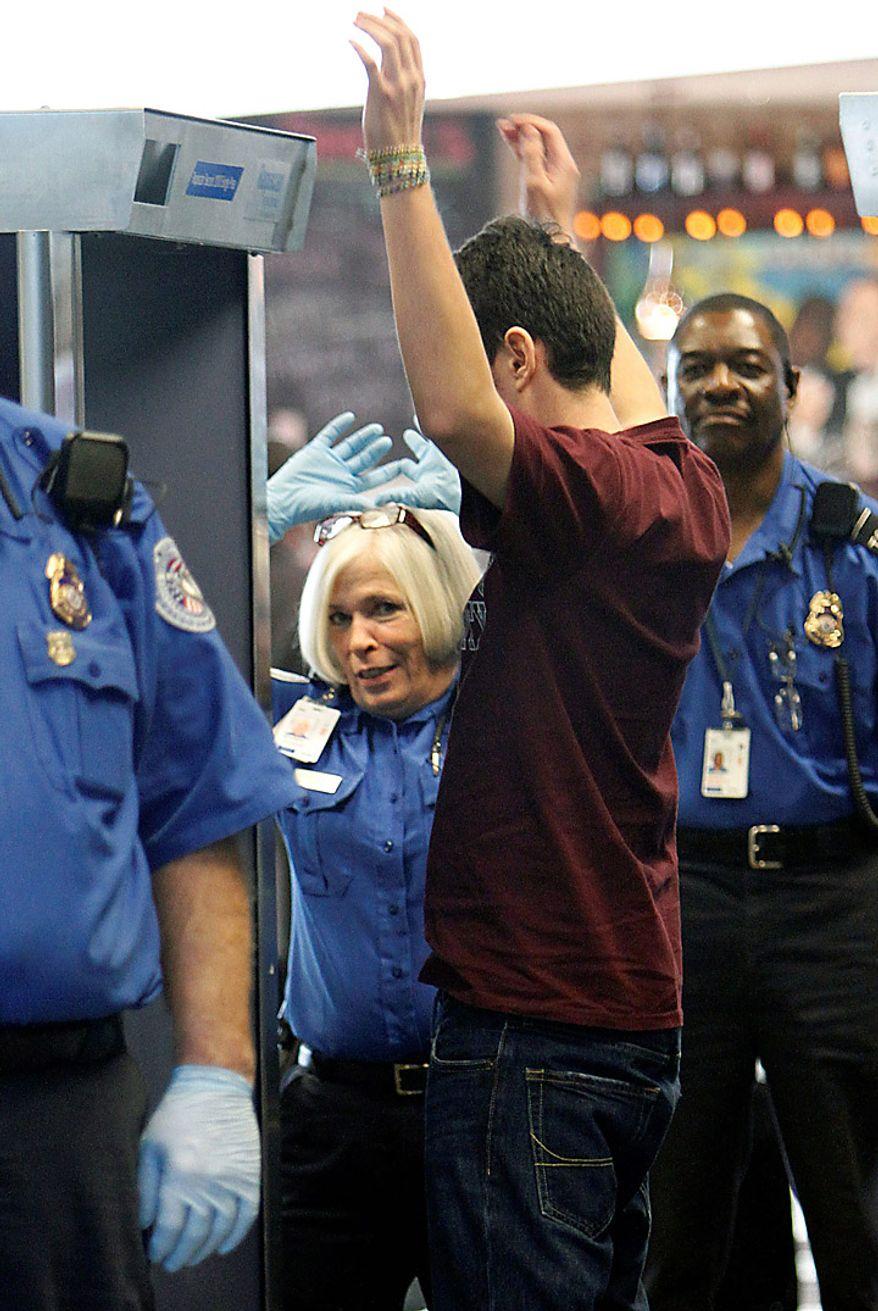 A passenger goes through a full-body scanner at Logan International Airport in Boston, Wednesday, Nov. 24, 2010. (AP Photo/Michael Dwyer)