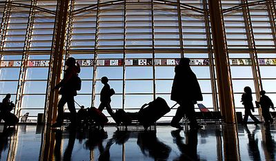 Travelers walk through the terminal at Washington's Ronald Reagan Washington National Airport, Wednesday, Nov. 24, 2010, as they holiday travel season began. (AP Photo/Alex Brandon)