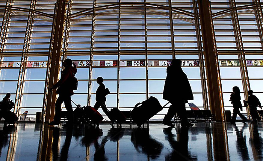 Travelers walk through the terminal at Washington's Ronald Reagan Washington National Airport, Wednesday, Nov. 24, 2010, as they holiday travel season began. (AP Photo/Alex Brandon)
