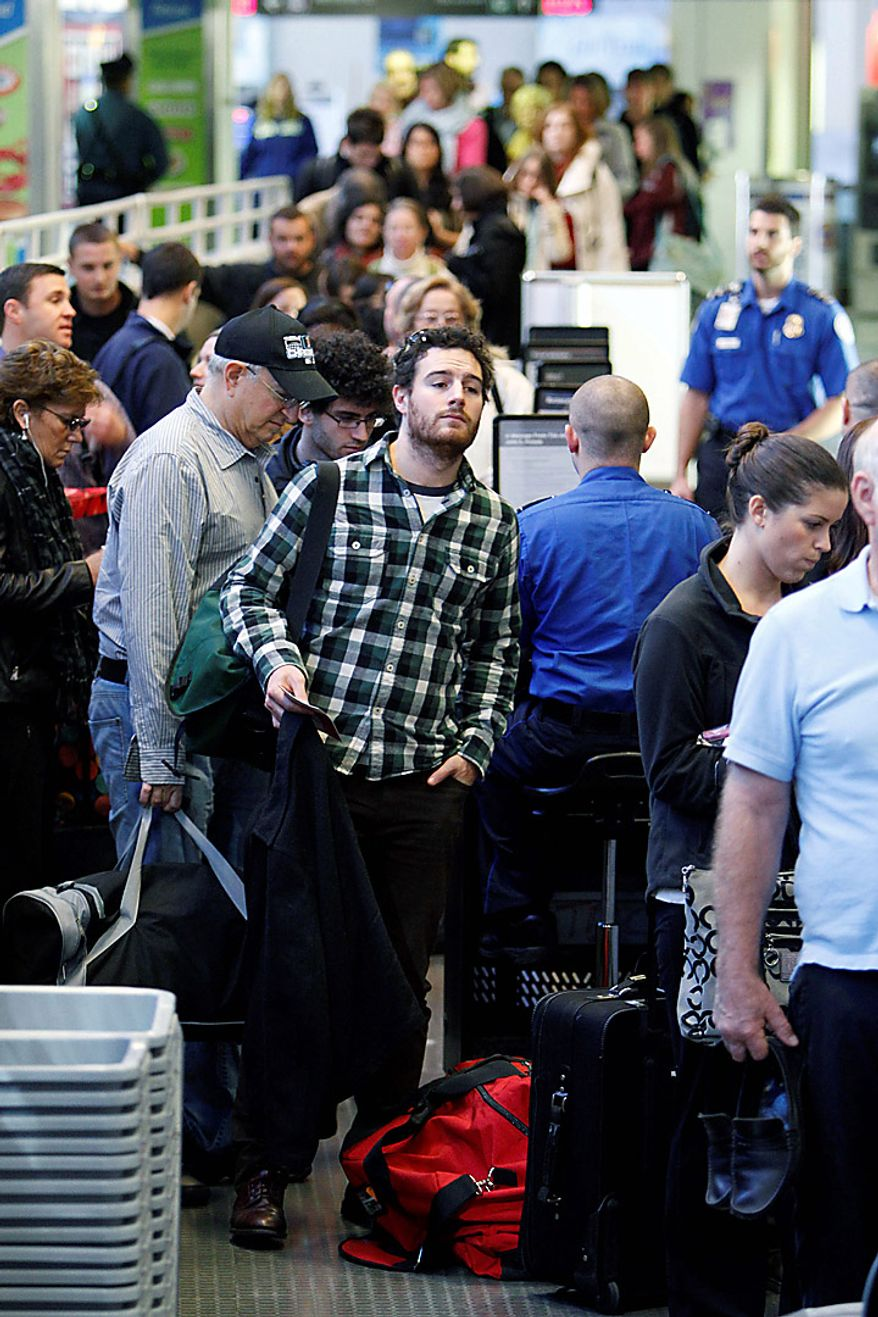 Travelers wait to pass through a security checkpoint at Logan International Airport in Boston, Wednesday, Nov. 24, 2010. (AP Photo/Michael Dwyer)