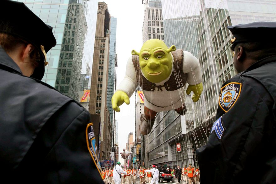 Members of the New York Police Department stand by as the Shrek balloon makes its way across 42nd Street during the Macy's Thanksgiving Day Parade on Thursday in New York. (Associated Press)