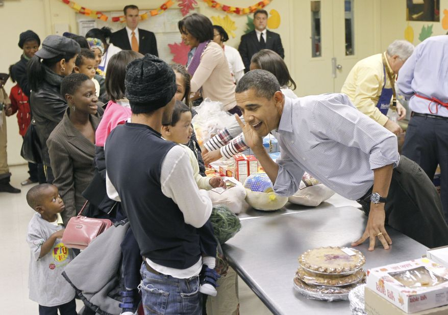 President Obama leans over to hear an unidentified child speak as he helps pack food for Thanksgiving at Martha's Table, a local food pantry in Washington, Wednesday, Nov. 24, 2010. (AP Photo/Pablo Martinez Monsivais)