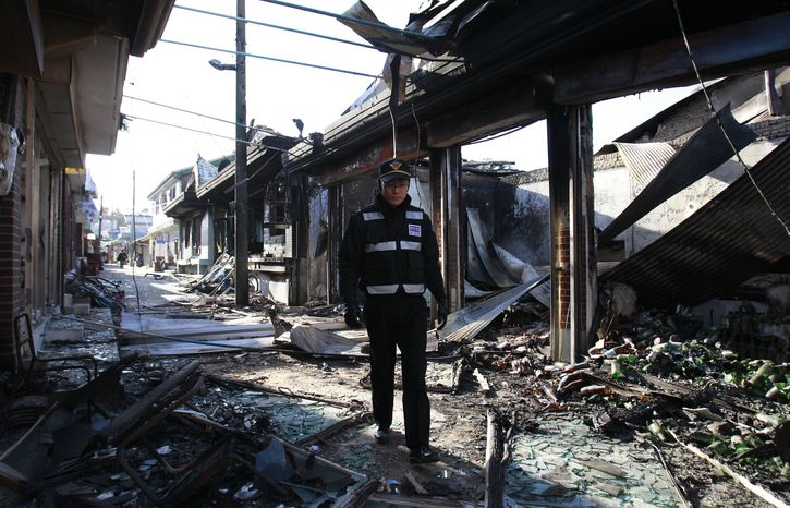 A South Korean police officer patrols near the destroyed houses on Yeonpyeong Island, South Korea, Thursday, Nov. 25, 2010. (AP Photo/ Lee Jin-man)