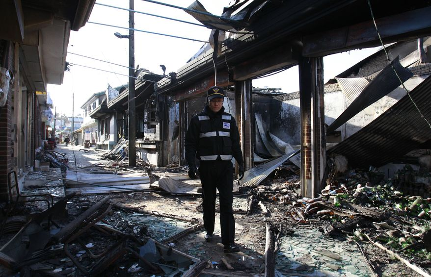A South Korean police officer patrols near the destroyed houses on Yeonpyeong Island, South Korea, Thursday, Nov. 25, 2010. (AP Photo/ Lee Jin-man)