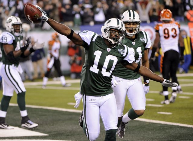 New York Jets wide receiver Santonio Holmes (10) celebrates after scoring a touchdown as teammates Dustin Keller (81) and Tony Richardson (49) and Cincinnati Bengals' Frostee Rucker (92) look on during the third quarter of an NFL football game at New Meadowlands Stadium, Thursday, Nov. 25, 2010, in East Rutherford, N.J. (AP Photo/Bill Kostroun)