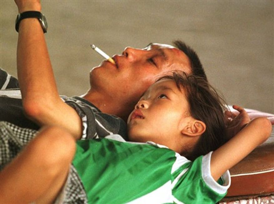 A Chinese man smokes a cigarette while reading to his daughter in Beijing, Aug. 25, 1997. (Associated Press) ** FILE **