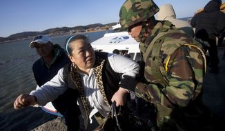 "A South Korean marine helps a woman disembark from a ferry ship Thursday as she returns to her home on Yeonpyeong Island. South Korea's president vowed to boost troops on the island targeted by a North Korean artillery barrage, while the North stridently warned of additional attacks if the South carries out any ""reckless military provocations."" (Associated Press)"