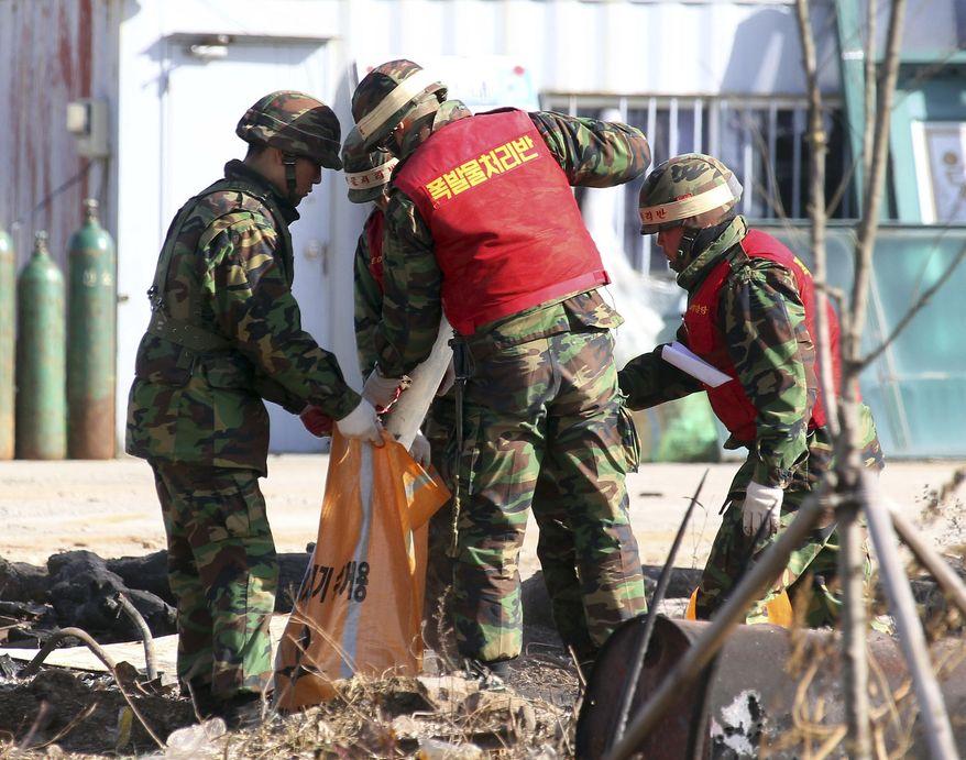 South Korean marines collect an unexploded shell fired from North Korea into a straw bag on Yeonpyeong island, South Korea, Thursday, Nov. 25, 2010. (AP Photo/Yonhap, Park Ji-ho)