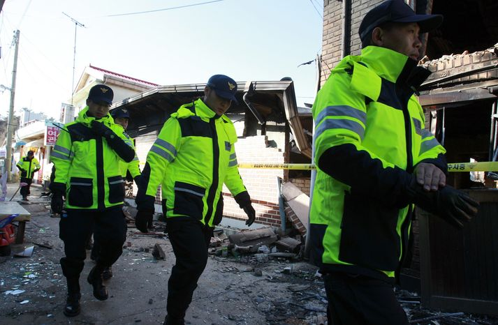 Police officers patrol near houses destroyed by North Korean shelling on the Yeonpyeong Island, South Korea, Friday, Nov. 26, 2010. North Korea warned Friday that planned U.S.-South Korean military drills are pushing the peninsula to the brink of war. (AP Photo/Lee Jin-man)