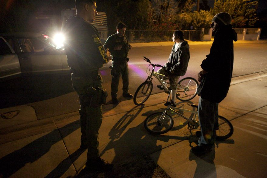 While patrolling in Cathedral City, Calif., police Officer Miguel Torres (left) and Mr. LaBella (second from left) stop teenagers who were riding bicycles without lights.