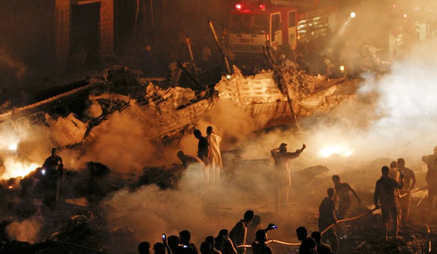 Volunteers and firefighters struggle to extinguish a fire at the site of a plane crash in Karachi, Pakistan, on Sunday, Nov. 28, 2010. A Russian cargo plane crashed into a housing complex in Pakistan's largest city soon after takeoff Sunday, setting off a huge blaze. (AP Photo/Shakil Adil)