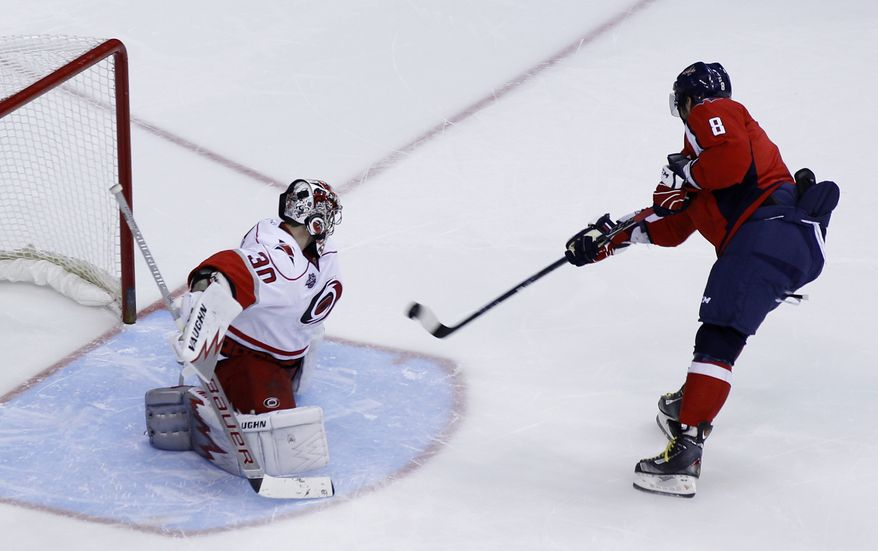 Washington Capitals' Alex Ovechkin (8), of Russia, scores the winning goal against Carolina Hurricanes goalie Cam Ward (30) during a shootout of an NHL hockey game Sunday, Nov. 28, 2010, in Washington. The Capitals won 3-2 in a shootout. (AP Photo/Luis M. Alvarez)