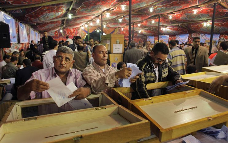 Electoral workers count ballots at a counting center after polls closed in the Abdeen neighborhood of Cairo on Sunday, Nov. 28, 2010. Egypt's parliamentary election was marred by scattered violence, reports of vote buying and the ejection of many independent monitors from polling stations amid what opponents say is a government campaign to clamp down at a time of political uncertainty. (AP Photo/Ben Curtis)