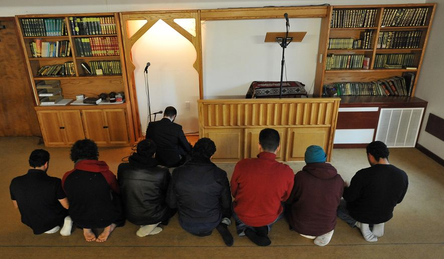 Imam Yosef Wanly (upper center) leads a prayer service at the Salman Al-Farisi Islamic Center in Corvallis, Ore., on Saturday, Nov. 27, 2010. Mohamed Osman Mohamud, 19, a former Oregon State University student who allegedly planned a bombing in Portland, Ore., during Friday's Christmas-tree-lighting ceremony, attended the center, which was struck by fire on Sunday. (AP Photo/Steve Dykes)