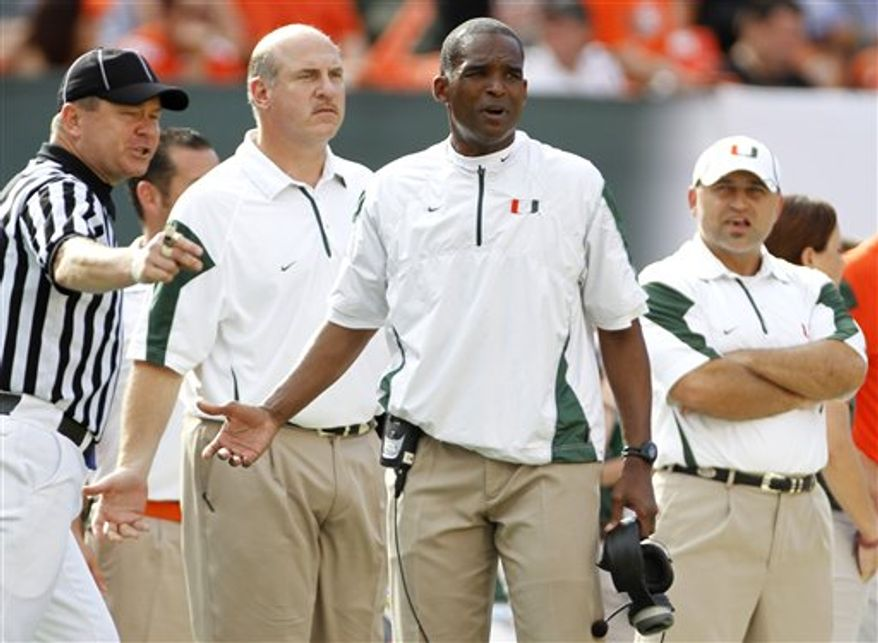 Miami coach Randy Shannon, right center, protests a foul call during the second half of an NCAA college football game against South Florida, Saturday, Nov. 27, 2010, in Miami. South Florida won 23-20 in overtime. (AP Photo/J Pat Carter)