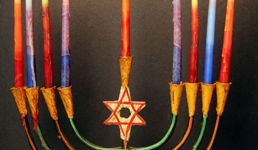 ASSOCIATED PRESS Jews use the menorah to help celebrate Hahukkah, which begins at sunset on Dec. 24 this year. **FILE**
