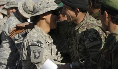 U.S. Army and Afghan army soldiers attached to the 1st Battalion, 502nd Infantry Regiment, 101st Airborne Division, congratulate each other during a training program graduation in Panjwai district in Afghanistan's Kandahar province on Monday, Nov. 29, 2010. (AP Photo/Alexander Zemlianichenko)
