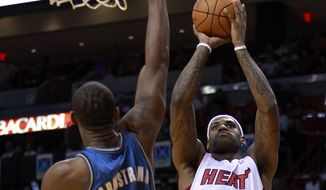 Miami Heat's LeBron James (6) shoots as Washington Wizards' Hilton Armstrong (24) defends in the first quarter of an NBA basketball game in Miami, Monday, Nov. 29, 2010. (Associated Press)