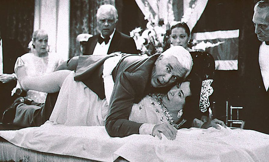 """This 1988 publicity file photo provided by Paramount Pictures shows actor Leslie Nielsen, center top, with actress Jeannette Charles,  portraying the Queen of England, in a scene from """"The Naked Gun"""". The Canadian-born Nielsen, who went from drama to inspired bumbling as a hapless doctor in """"Airplane!"""" and the accident-prone detective Frank Drebin in """"The Naked Gun"""" comedies, has died. He was 84. His agent John S. Kelly said Nielsen died Sunday, Nov. 28, 2010, at a hospital near his home in Florida where he was being treated for pneumonia. (AP Photo/Paramount Pictures, Elliott Marks, File)"""