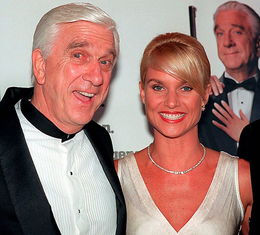 """In this file  photo taken May 16, 1996, actors Leslie Nielsen, left, and Nicollette Sheridan arrive at the El Capitan Theatre in Los Angeles for the premiere of """"Spy Hard."""" The Canadian-born Nielsen, who went from drama to inspired bumbling as a hapless doctor in """"Airplane!"""" and the accident-prone detective Frank Drebin in """"The Naked Gun"""" comedies, has died. He was 84. His agent John S. Kelly said Nielsen died Sunday, Nov. 28, 2010, at a hospital near his home in Florida where he was being treated for pneumonia. (AP Photo/Michael Caulfield, File)"""