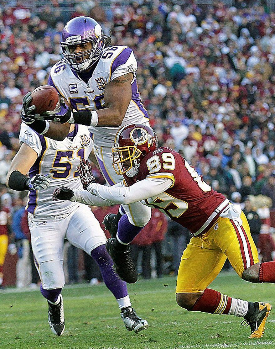 Minnesota Vikings linebacker Heath Farwell, top, intercepts a pass intended for Washington Redskins wide receiver Santana Moss (89) during the second half of an NFL football game in Landover, Md., Sunday, Nov. 28, 2010. (AP Photo/Pablo Martinez Monsivias)