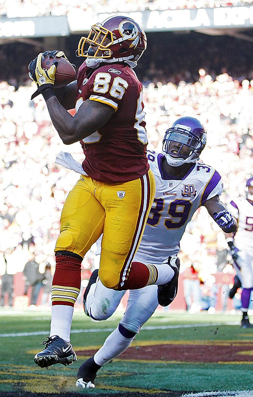 Washington Redskins tight end Fred Davis (86) pulls in a touchdown-pass under pressure from Minnesota Vikings safety Husain Abdullah during the first half of an NFL football game in Landover, Md., Sunday, Nov. 28, 2010. (AP Photo/Evan Vucci)
