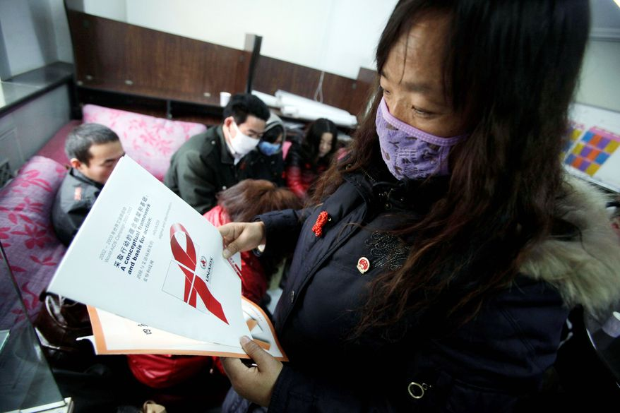 ASSOCIATED PRESS PHOTOGRAPHS A woman who contracted AIDS looks through pamphlets as she attends a press conference to highlight the plight of AIDS sufferers in Beijing on Tuesday.