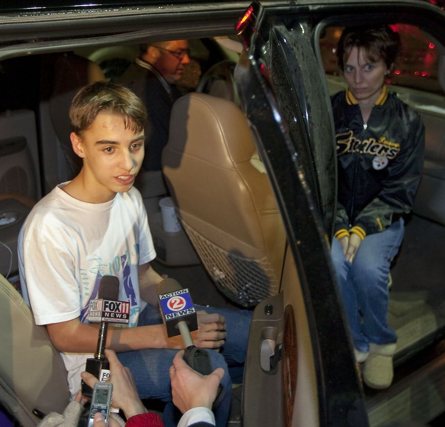 Austin Biehl talks to reporters on Monday night, Nov. 29, 2010 in Marinette, Wis., about being taken hostage at Marinette High School by another student earlier in the day, as his mother Carla looks on at right. (AP Photo/Mike Roemer)