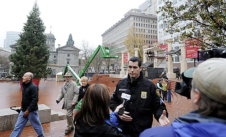 Portland police sergeant Pete Simpson is interviewed in front of the Christmas tree in Pioneer square on Saturday Nov. 27, 2010 in Portland, Ore., the morning after a car bomb plot was foiled during the annual tree lighting ceremony. Federal agents in a sting operation arrested a Somali-born teenager just as he tried blowing up a van he believed was loaded with explosives at the crowded event, authorities said. (AP Photo/Greg Wahl-Stephens)