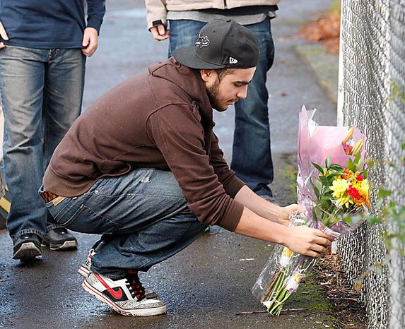 Worshipper Osama Abdelli leaves flowers by the side of the Salman Al-Farisi Islamic Center in Corvallis, Ore. Sunday, Nov. 28, 2010, where an alleged arsonist set a fire in the early morning hours. Anger on Sunday over a Somali-born teen's failed plan to blow up a van full of explosives during Portland's Christmas tree lighting ceremony apparently erupted in arson on Sunday when a fire damaged the Islamic center once frequented by the suspect. (AP Photo/Rick Bowmer)