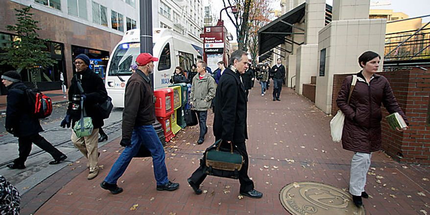 Commuters walk near Pioneer Courthouse Square, Monday, Nov. 29, 2010, in Portland, Ore.  Terror suspect Mohamed Osman Mohamud and an FBI operative parked a van full of dummy explosives across from Pioneer Courthouse Square just after sundown Friday while thousands gathered in the square for the annual tree lighting. Mohamud is accused of attempting to detonate the explosives. (AP Photo/Rick Bowmer)